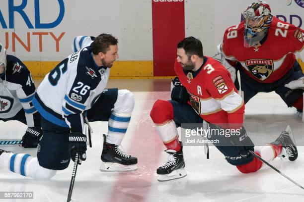 Keith Yandle of the Florida Panthers talks to Blake Wheeler of the Winnipeg Jets during the warm up at the BBT Center on December 7 2017 in Sunrise...