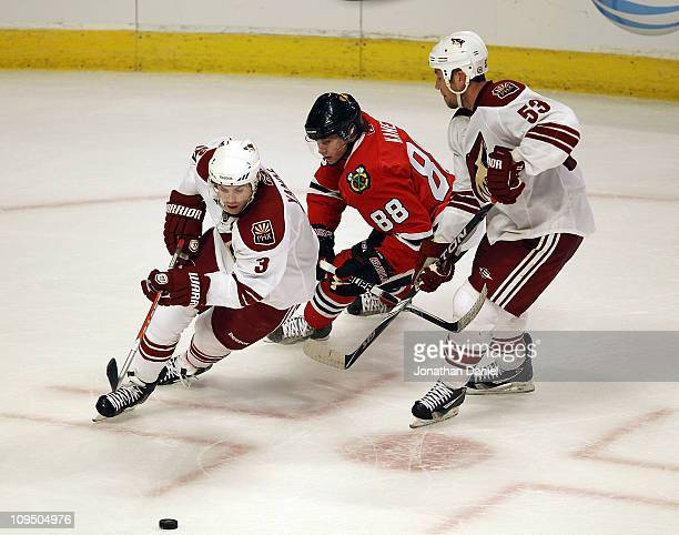 Keith Yandle of the Phoenix Coyotes and Patrick Kane of the Chicago Blackhawks chase down the puck as they skate around Derek Morris at the United...