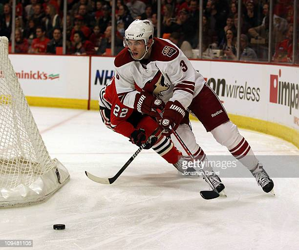 Keith Yandle of the Phoenix Coyotes chases down the puck behind the Coyote net in front of Troy Brouwer of the Chicago Blackhawks at the United...