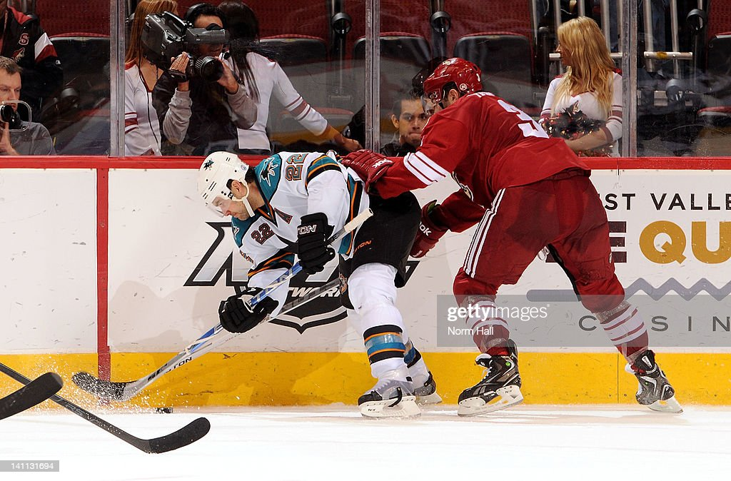 Keith Yandle #3 of the Phoenix Coyotes checks Dan Boyle #22 of the San Jose Sharks into the boards at Jobing.com Arena on March 10, 2012 in Glendale, Arizona.