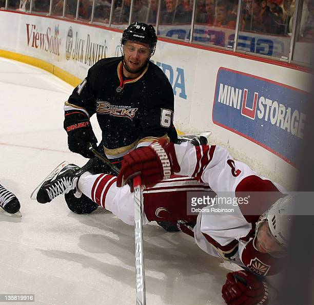 Keith Yandle of the Phoenix Coyotes falls to the ice against Brandon McMillan of the Anaheim Ducks during the game on December 14, 2011 at Honda...