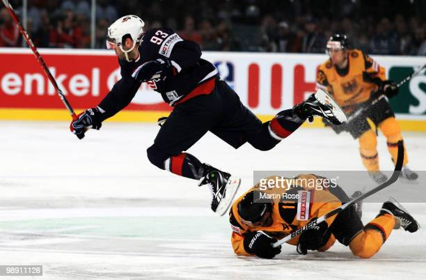 Keith Yandle of USA jumps over Sven Felski of Germany during the IIHF World Championship group D match between USA and Germany at Veltins Arena on...