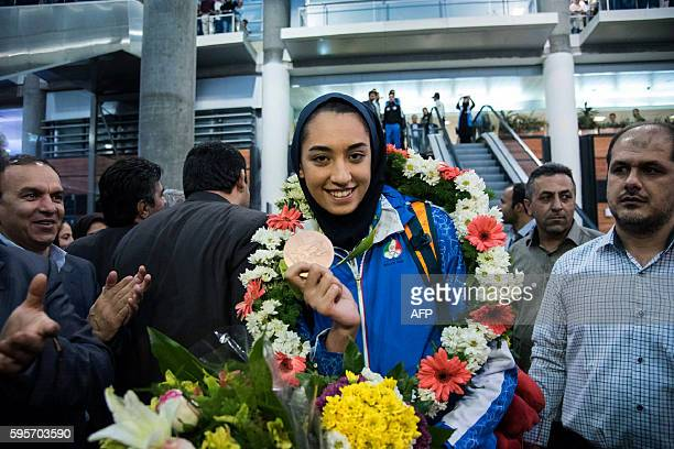 Keivan Alizadeh the father of Kimia Alizadeh who became the first Iranian woman ever to win an Olympic medal shows her medal upon her arrival at Imam...