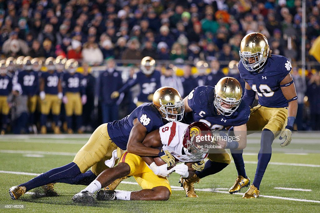 KeiVarae Russell #6 and Joe Schmidt #38 of the Notre Dame Fighting Irish tackle JuJu Smith-Schuster #9 of the USC Trojans in the second half of the game at Notre Dame Stadium on October 17, 2015 in South Bend, Indiana.