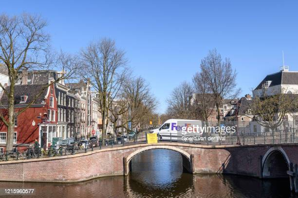Keizersgracht Bridge with a FedEx delivery truck in Amsterdam during a weekday morning following the advice of the Dutch government to stay at home...