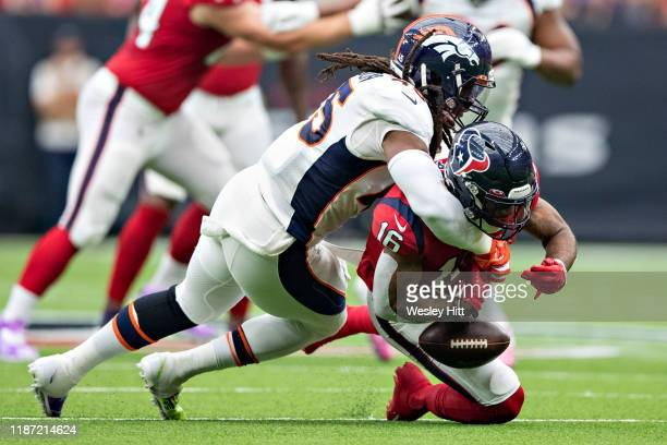 KeKe Coutee of the Houston Texans is hit after catching a pass and fumbles the ball by Alexander Johnson of the Denver Broncos during the first half...