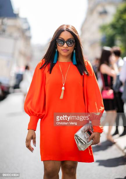 Keke Olisemeka wearing orange dress with long sleeves is seen on day four during Paris Fashion Week Haute Couture FW18 on July 4 2018 in Paris France