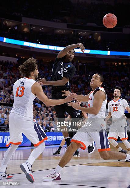 Kelan Martin of the Butler Bulldogs throws a pass against Anthony Gill and Malcolm Brogdon of the Virginia Cavaliers in the first half during the...