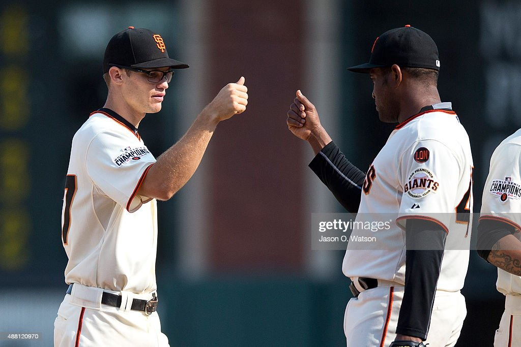 Kelby Tomlinson #37 of the San Francisco Giants celebrates with Alejandro De Aza #45 after the game against the San Diego Padres at AT&T Park on September 13, 2015 in San Francisco, California. The San Francisco Giants defeated the San Diego Padres 10-3.
