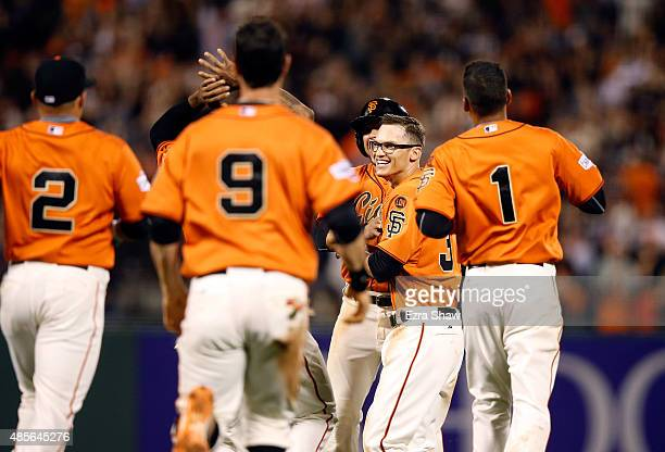 Kelby Tomlinson of the San Francisco Giants is congratulated by teammates after he had the gamewinning hit in the bottom of the ninth inning that...