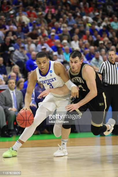 Keldon Johnson of the Kentucky Wildcats drives against Fletcher Magee of the Wofford Terriers during the second half of the game in the second round...