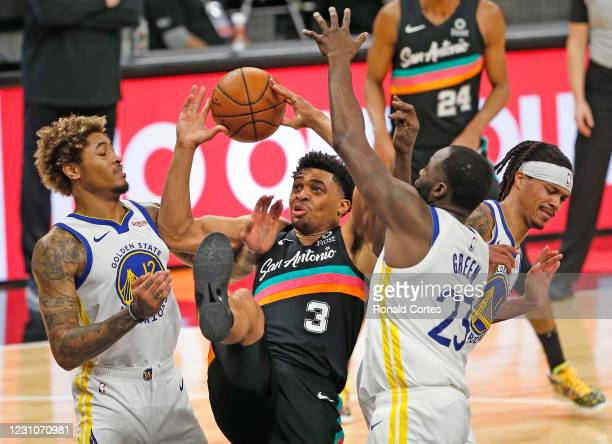 Keldon Johnson of the San Antonio Spurs fights for a rebound with Kelly Oubre Jr. #12 and Draymond Green of the Golden State Warriors in the first...
