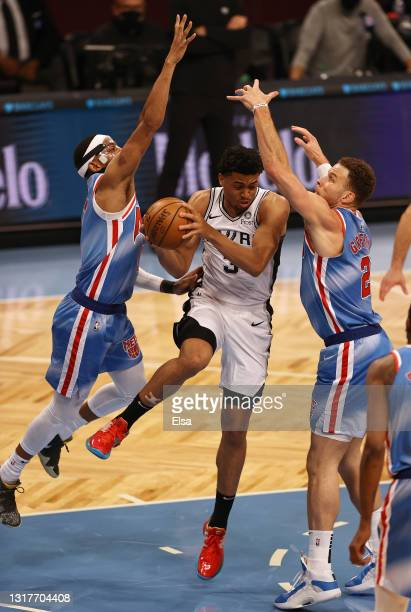 Keldon Johnson of the San Antonio Spurs tries to get by Bruce Brown and Blake Griffin of the Brooklyn Nets in the first quarter at Barclays Center on...