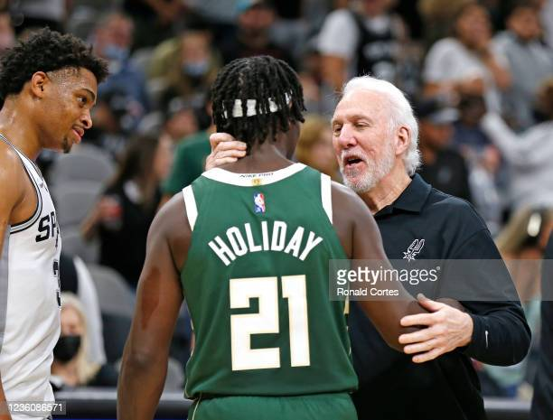 Keldon Johnson of the San Antonio Spurs watches as head coach Gregg Popovich chats with Drew Holiday of the Milwaukee Bucks at the end of the game at...