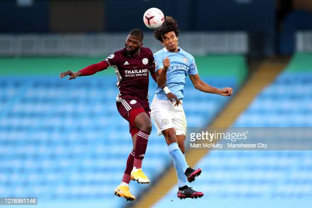Kelechi Iheanacho of Leicester City jumps for a header with Nathan Ake of Manchester City during the Premier League match between Manchester City and...