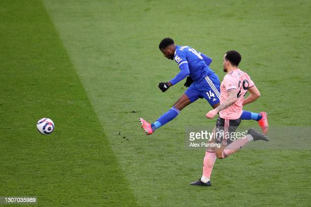 Kelechi Iheanacho of Leicester City scores their side's third goal whilst under pressure from Kean Bryan of Sheffield United during the Premier...