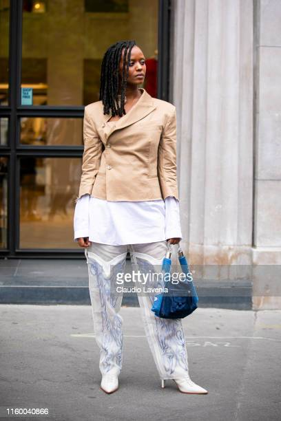 Kelela, wearing a beige blazer, white decorated pants, white heels and blue bag, is seen outside Schiaparelli show during Paris Fashion Week - Haute...