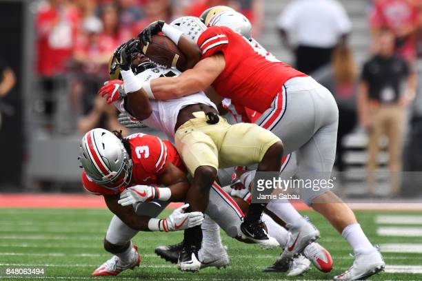 Kell Walker of the Army Golden Knights is tackled by Damon Arnette of the Ohio State Buckeyes and Sam Hubbard of the Ohio State Buckeyes in the first...