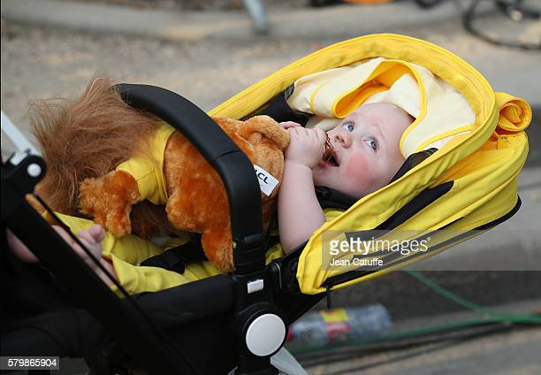 Kellan Froome son of Chris Froome of Great Britain and Team Sky bites the lion plush given to the leader's of the Tour following stage 21 last stage...