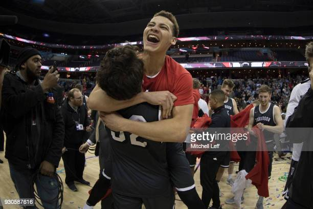 Kellan Grady of the Davidson Wildcats hugs Rusty Reigel after defeating the Rhode Island Rams in the Championship game of the Atlantic 10 Basketball...