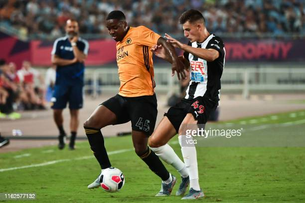 Kelland Watts of Newcastle United and Niall Ennis of Wolverhampton Wanderers compete for the ball during Premier League Asia Trophy match between...