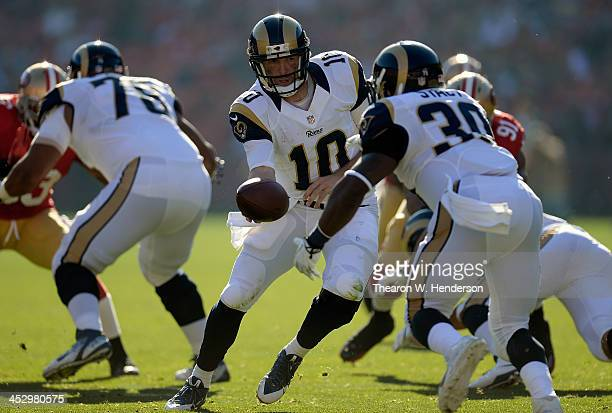 Kellen Clemens of the St Louis Rams turns to hand the ball off to running back Zac Stacy against the San Francisco 49ers at Candlestick Park on...