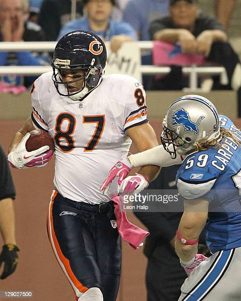 Kellen Davis of the Chicago Bears scores on a 9 yard pass from Jay Cutler in the second quarter as Bobby Carpenter of the Detroit Lions defends...