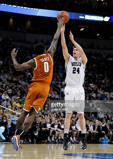 Kellen Dunham of the Butler Bulldogs shoots a three point basket over Kendal Yancy of the Texas Longhorns in the first half during the second round...