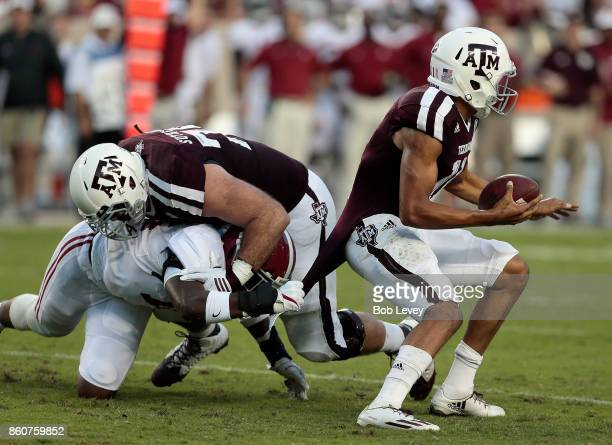 Kellen Mond of the Texas AM Aggies attempts to break the tackle attempt by Rashaan Evans of the Alabama Crimson Tide as he is blocked by Keaton...