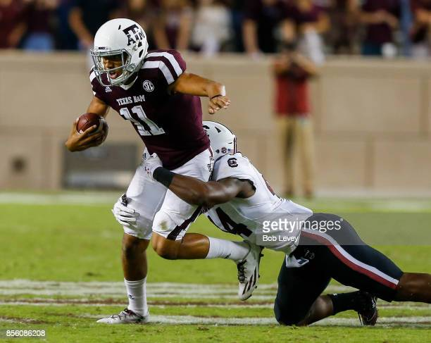 Kellen Mond of the Texas AM Aggies is brought down from behind by DJ Smith of the South Carolina Gamecocks in the third quarter at Kyle Field on...