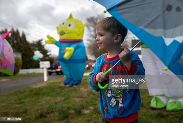 Kellen Shea, watches as a caravan of cars rides past to wish him a socially distanced happy third birthday in front of his family's home on March 28,...