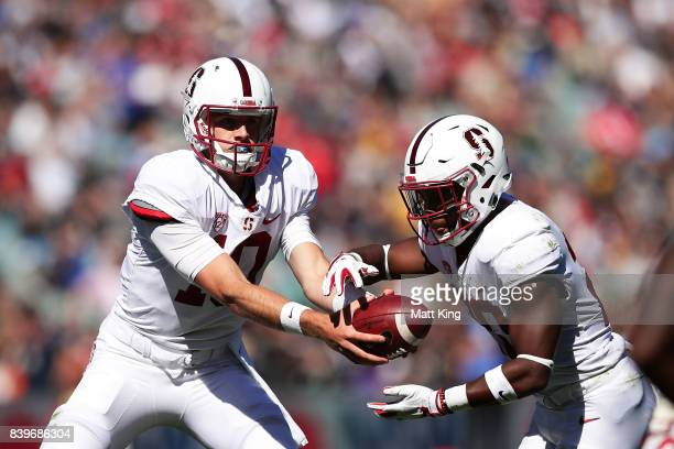 Keller Chryst of Stanford hands the ball off to Bryce Love of Stanford on the way to scoring a touchdown during the College Football Sydney Cup match...