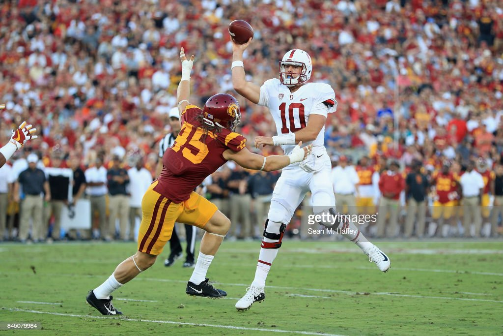 Keller Chryst #10 of the Stanford Cardinal throws a touchdown pass during the second quarter as he is pressured by Porter Gustin #45 of the USC Trojans at Los Angeles Memorial Coliseum on September 9, 2017 in Los Angeles, California.