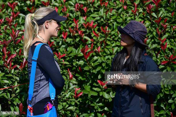 Kelley Cahill girlfriend of Jon Rahm of Spain and the mother of Xander Schauffele of the United States speak on the 17th hole during the first round...