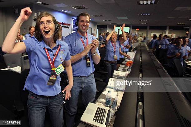 Kelley Clarke left celebrates as the first pictures appear on screen after a successful landing inside the Spaceflight Operations Facility for NASA's...