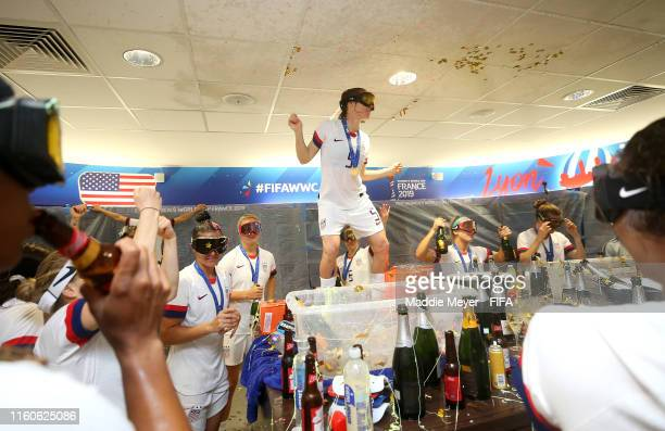Kelley O'hara of the USA celebrates with her teammates in the dressing room following their team's victory in the 2019 FIFA Women's World Cup France...