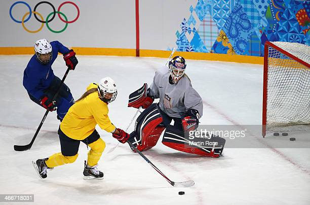 Kelli Stack of United States takes a shot past teammate goaltender Brianne McLaughlin during a training session ahead of the Sochi 2014 Winter...