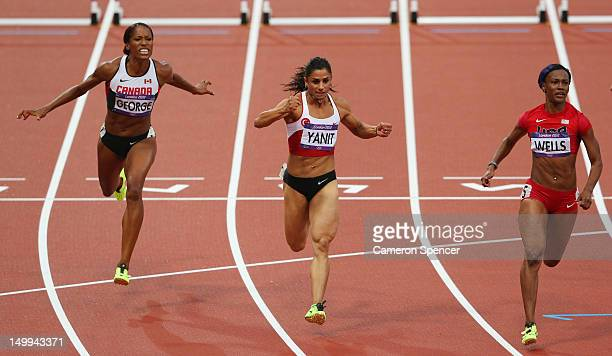 Kellie Wells of the United States leads Nevin Yanit of Turkey and Phylicia George of Canada competing in the Women's 100m Hurdles Semifinals on Day...
