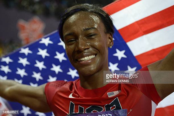 US' Kellie Wells waves her national flag after she won the bronze medal in the women's 100m hurdles final at the athletics event during the London...