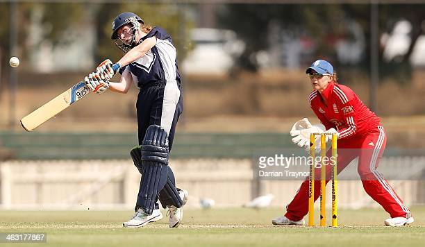 Kelly Applebee of Victoria hits a ball for 6 runs as wicketkeeper Amy Jones of England looks on during the International Tour match between the...