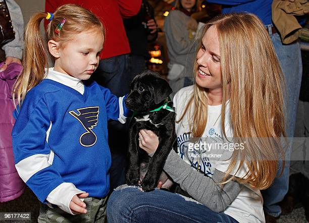 Kelly Backes wife of St Louis Blues' David Backes shows a puppy available for adoption to a young fan before the game against the Anaheim Ducks on...