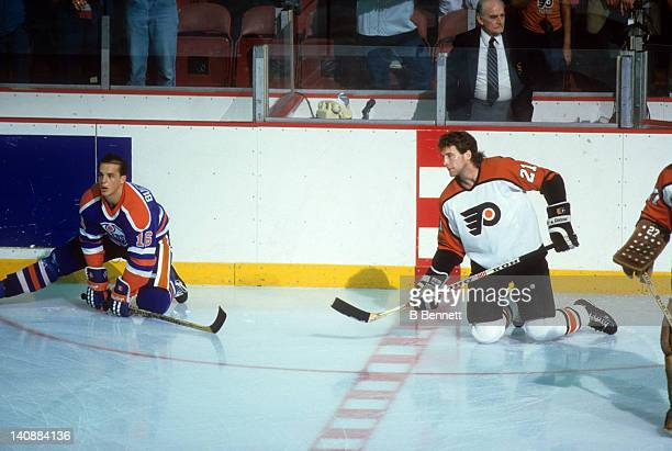 Kelly Buchberger of the Edmonton Oilers and Dave Brown of the Philadelphia Flyers stretch on the ice before Game 3 of the 1987 Stanley Cup Finals on...