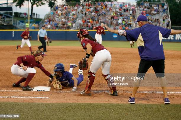 Kelly Burdick of the Washington Huskies dives safely back into first base under the tag of Carsyn Gordon of the Florida State Seminoles during the...