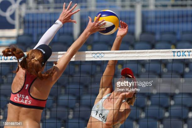 Kelly Claes of Team United States attempts to block the hit by Heather Bansley of Team Canada during the Women's Round of 16 beach volleyball on day...