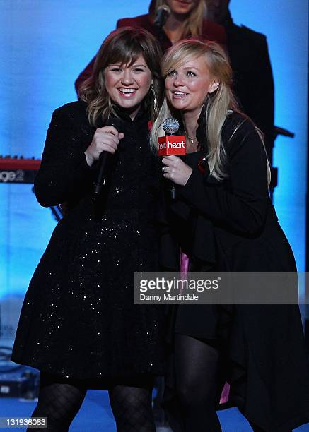 Kelly Clarkson and Emma Bunton hug each other on stage after Kelly Clarkson's performance during the switchon of Regent Street's Christmas lights...