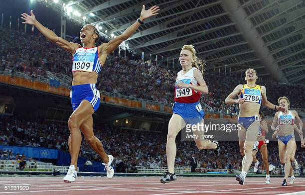 Kelly Holmes of Great Britain celebrates as she crosses the finish line as she win's gold in the women's 1500 metre final on August 28 2004 during...