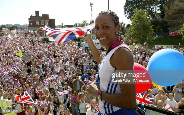 Kelly Holmes waves the Union Jack to the crowds during an open toppedbus tour parade held in honour of the doubleOlympic gold medallist through...
