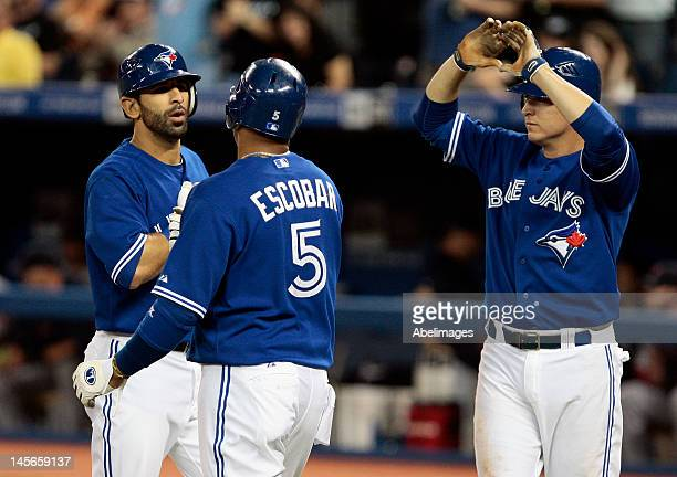 Kelly Johnson Jose Bautista and Yunel Escobar of the Toronto Blue Jays celebrate Jose Bautista 3run home runduring MLB action at The Rogers Centre...