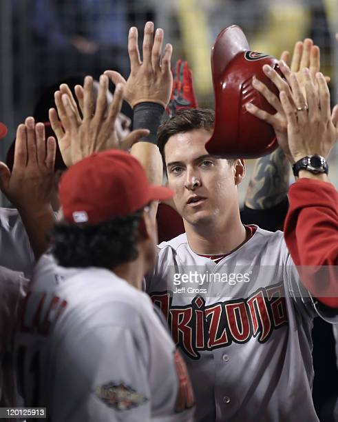 Kelly Johnson of the Arizona Diamondbacks receives high fives in the dugout after scoring a run on a double by Justin Upton against the Los Angeles...