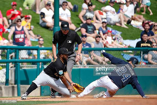 Kelly Johnson of the Atlanta Braves slides into third base with a triple ahead of the throw to Jason Rogers of the Pittsburgh Pirates in the fifth...